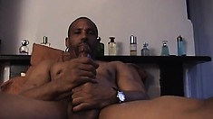 Hung black stud lies fully naked on the bed jerking his huge rod until he cums