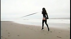 Curvy slave is tied up and leashed and led around on the beach