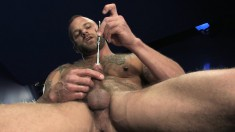 Tattooed and pierced macho man eases a metal rod into his cock in a sounding session