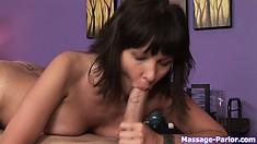After licking his lollipop, this hot brunette masseuse slides it between her titties