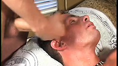 Sexy tanned guy has two studs filling his mouth and his anal hole with their dicks