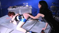 Dominant mistress dishes out some cruel punishment to a redhead slave